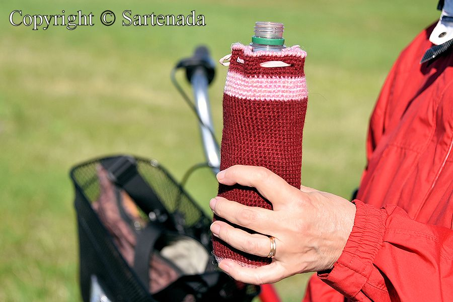 Drinking bottle and its crocheted cover. Crocheted cover keeps in summer the water inside cool and in the winter, the water does not freeze